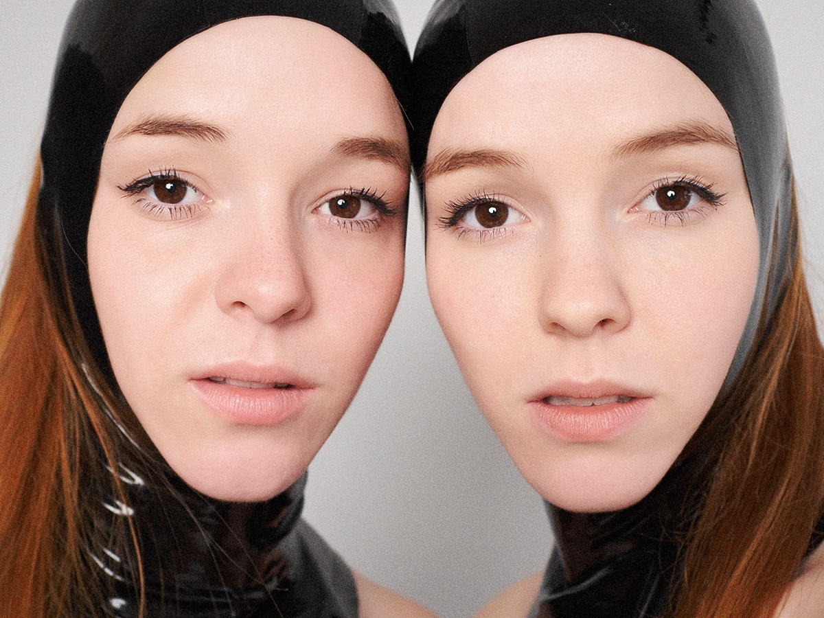 Close up photo of the Reyes Twins, Naomi & Ruth wearing black latex hoods.